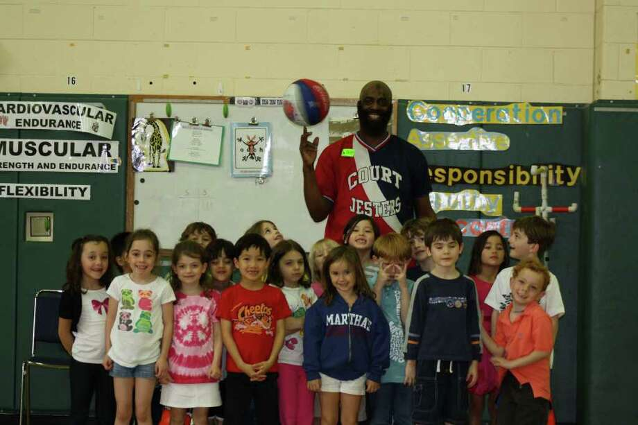 Rainbow, back, of the Court Jesters basketball team teaches skills to Greens Farms Elementary School students. The Court Jesters will play against the Westport Faculty All-Stars Friday at 7 p.m. Photo: Contributed Photo