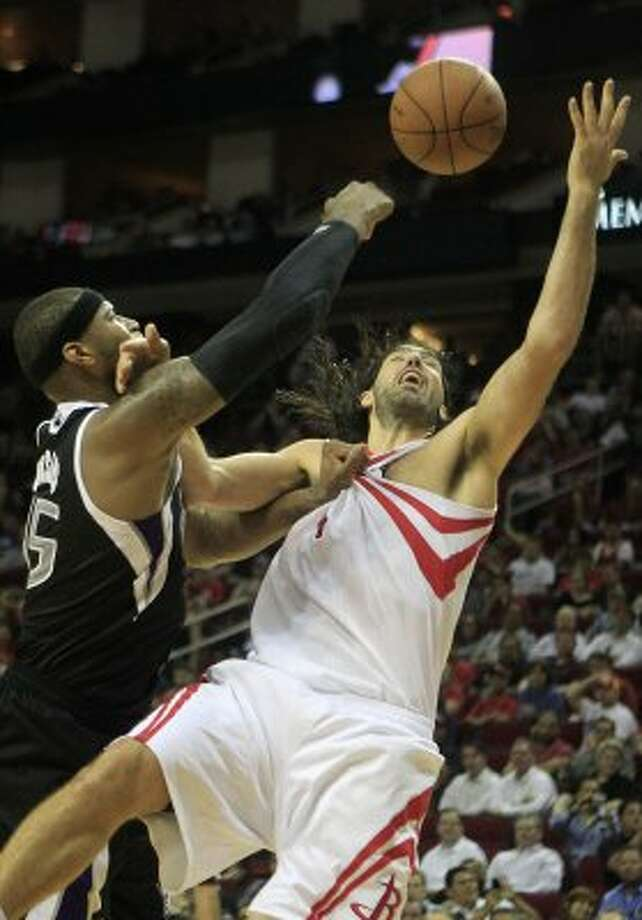 Kings power forward DeMarcus Cousins, left, fights for possession of the ball over Rockets power forward Luis Scola in the second half. (Cody Duty / Chronicle)