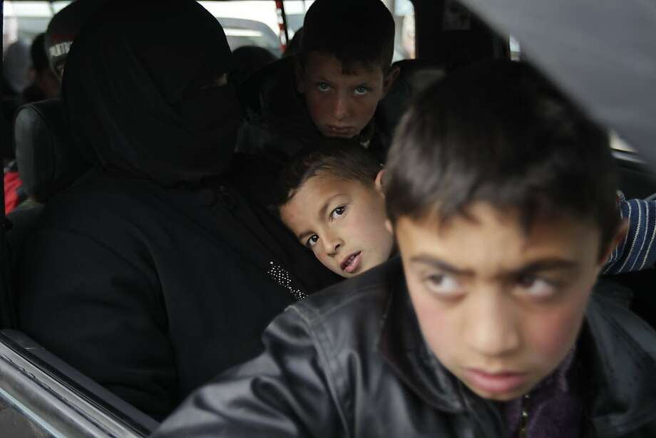 Syrian refugees who fled the violence in the Syrian town of Qusayr arrive to the Lebanese city of Arsal in the Bekaa Valley aboard a bus after crossing through Lebanon's northern border with Syria on March 26, 2012. UN-Arab League envoy Kofi Annan said that only Syrians could determine President Bashar-al-Assad's fate and called for the rival sides to negotiate an end to the conflict. AFP PHOTO/JOSEPH EID (Photo credit should read JOSEPH EID/AFP/Getty Images) Photo: Joseph Eid, AFP/Getty Images