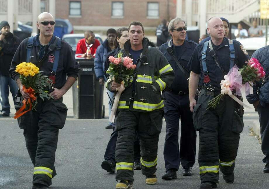 Sunday afternoon, Bridgeport fire fighters, (L-R) John Harring, Frank Mercado and Thomas Connolly carry roses to a makeshift memorial on the steps to Black's second-story apartment, at the P.T. Barnum apartments, where the single mother died with her twin girls, Nyasija and Tyasija Williams, both 4, and son Nyshon Williams, 5, Friday. Sunday, Nov. 15, 2009. Photo: Phil Noel / Connecticut Post