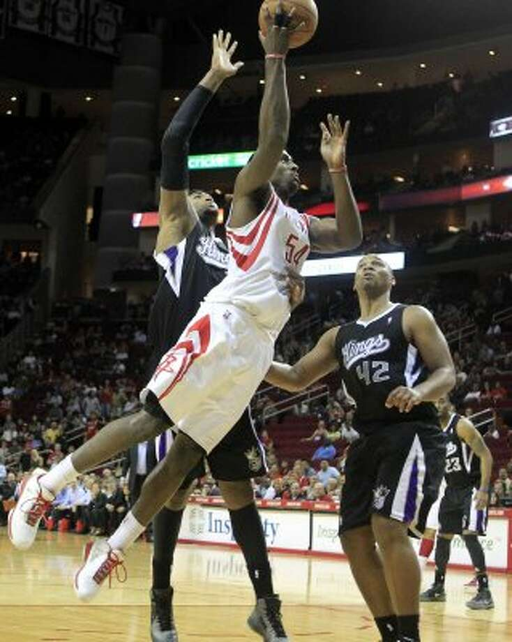 Rockets power forward Patrick Patterson (54) shoots over Kings power forward DeMarcus Cousins, left, and Kings center Chuck Hayes, right, during the second half  (Cody Duty / Chronicle)