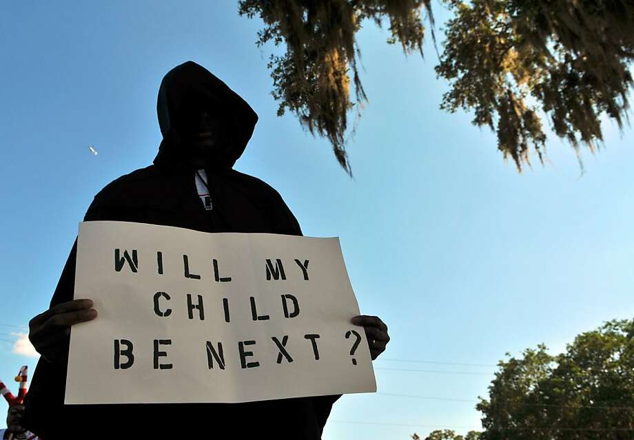 """SANFORD, FL- MARCH 26:  A man dressed in a hood holds up a sign saying """"Will My Child Be Next?"""", during a protest march just prior to a town hall meeting March 26, 2012 in Sanford, Florida. The teenager's family addressed the town hall meeting along with Rev. Al Sharpton. Martin was killed by George Michael Zimmerman while on neighborhood watch patrol in the city. (Photo by Roberto Gonzalez/Getty Images) Photo: Roberto Gonzalez, Getty Images"""