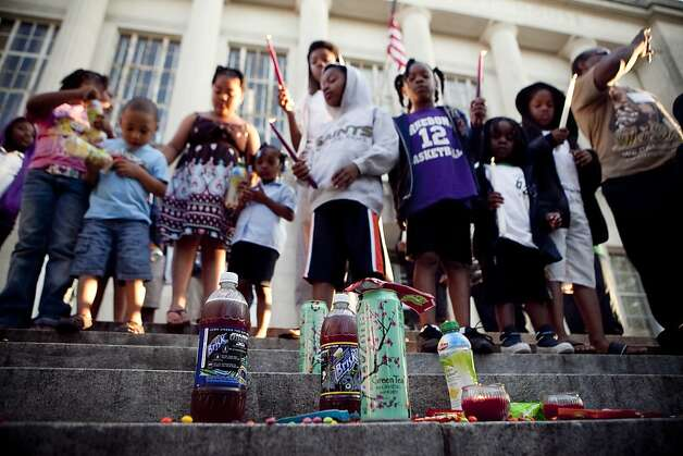 Children stand in front of piles of Skittles and bottles of tea during a vigil for Trayvon Martin where about 125 people gathered Monday, March 26, 2012  in Courthouse Square in Houma, La. The17-year-old Martin was killed by neighborhood watch volunteer George Zimmerman in Sanford, Fla. on Feb. 26. (AP Photo/The Houma Daily Courier, Julia Rendleman) Photo: Julia Rendleman, Associated Press