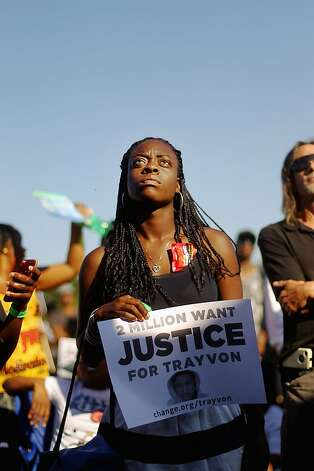SANFORD, FL - MARCH 26:   Trayvon Martin supporters gather at a rally while listening to an overflow broadcast of a town hall meeting about Martin's death on March 26, 2012 in Sanford, Florida. The teenager's family addressed the town hall meeting along with Rev. Al Sharpton. Martin was killed by George Michael Zimmerman while on neighborhood watch patrol in the city.  (Photo by Mario Tama/Getty Images) Photo: Mario Tama, Getty Images