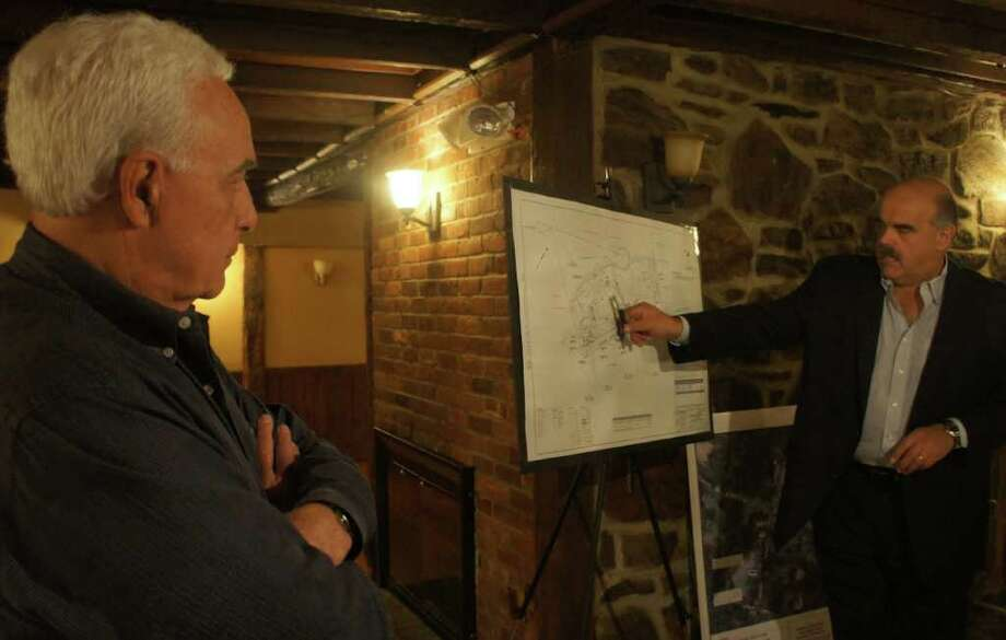 Larry Weisman, left, the land-use lawyer for Chabad of Westport, and Peter Romano, a partner at Land-Tech Consultants, discuss Chabad's plans for 79 Newtown Turnpike during a neighborhood meeting Monday. Photo: Paul Schott / Westport News