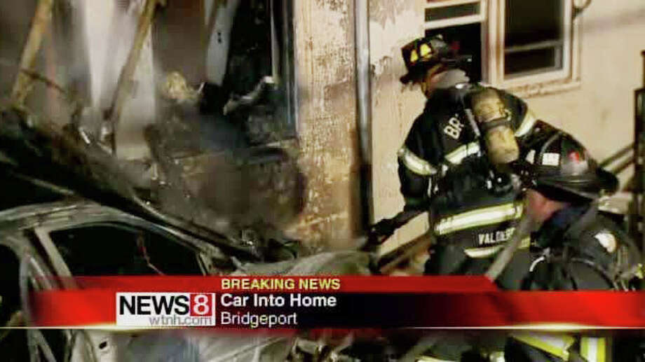 Two women were hospitalized after a car crashed into a house at 75 Stewart St. in Bridgeport, Conn. early on the morning of Tuesday, March 27, 2012 and caught fire. Photo: Contributed Photo