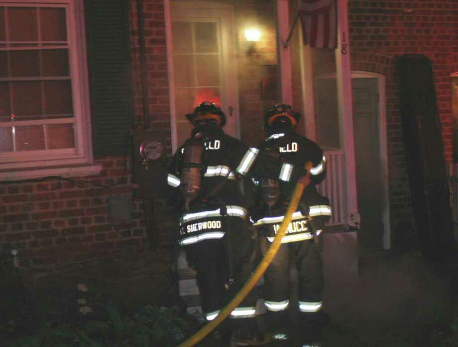 Fairfield firegihters prepare to attack a fire that ignited early Tuesday on the porch of a Plum Street home. Photo: Fairfield Fire Department / Fairfield Citizen contributed