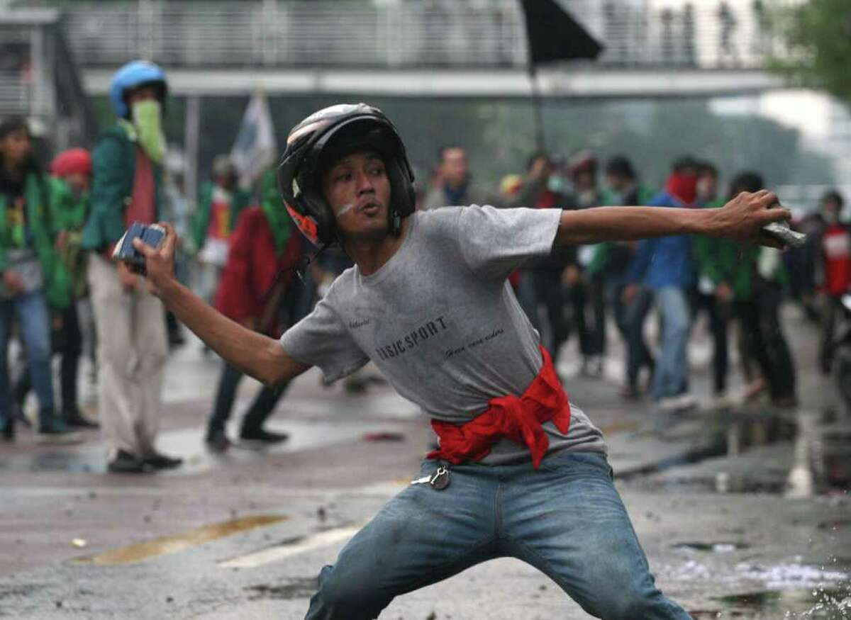 A student protester throws a rock at riot police during a protest against the government's plan to raise fuel prices in Jakarta, Indonesia, Tuesday, March 27, 2012. Police fired tear gas and water canons to disperse thousands of rock-throwing Indonesians protesting plans to push up fuel prices by more than 30 percent.