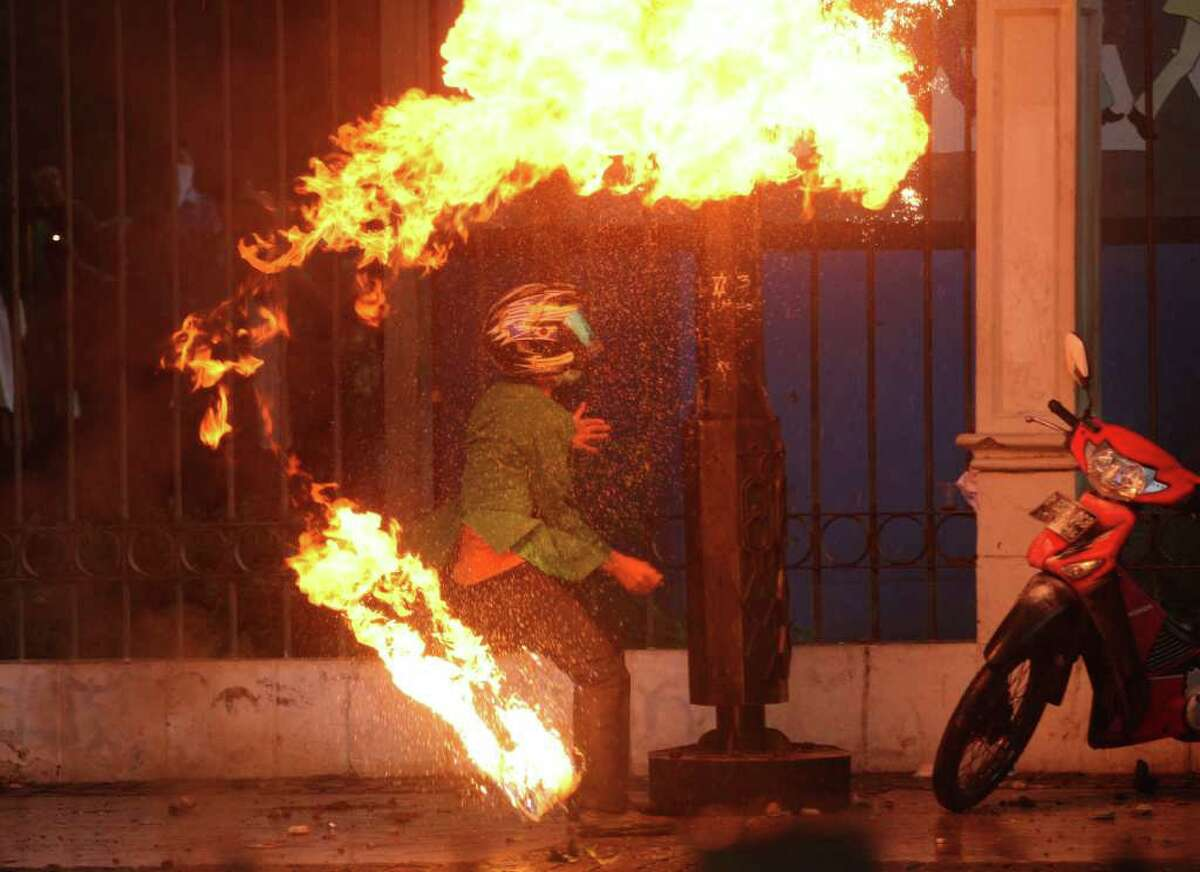 A student protester throws a molotov caocktail at riot police during a protest against the government's plan to raise fuel prices in Jakarta, Indonesia, Tuesday, March 27, 2012. The Indonesian government plans to raise fuel prices by about 33 percent next month to avoid a budget deficit due to expensive fuel subsidies.