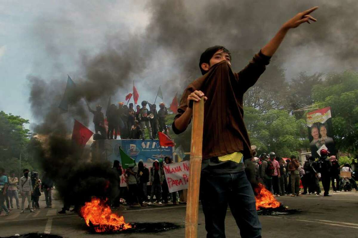 Student protesters burn tires during a protest against the government's plan to raise fuel prices in Medan, North Sumatra, Indonesia, Tuesday, March 27, 2012. The Indonesian government plans to raise fuel prices by about 33 percent next month to avoid a budget deficit due to expensive fuel subsidies.