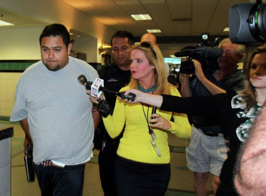 Shooting suspect Simon Rene Garcia (left) is escorted out of the San Antonio Police Department on Tuesday morning, March 27, 2012. Garcia was arrested in connection with the fatal shooting of Sam Wass in the 100 block of San Juan on Monday. Photo: John Davenport, San Antonio Express-News