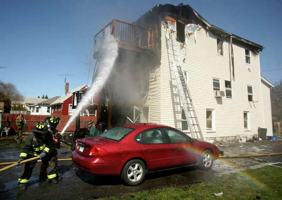 Firefighters pour water on a fire in the third floor unit of a multifamily house at 215 Garibaldi Avenue in Stratford on Tuesday morning, March 27, 2012. Photo: Brian A. Pounds / Connecticut Post