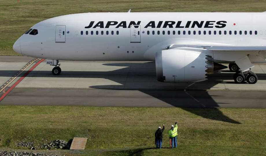 Boeing employees wave to the first Japan Airlines Boeing 787 airplane to be delivered as it is towed toward the runway prior to takeoff, Monday, March 26, 2012, in Everett, Wash. It was the first 787 delivered with GEnx engines. Photo: AP