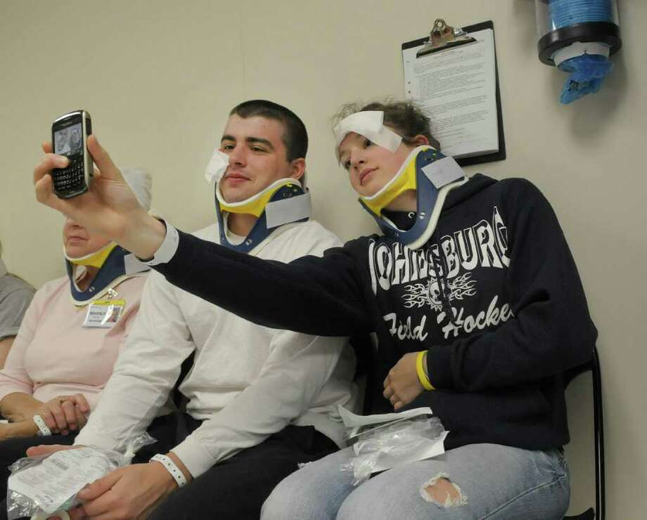 James Rizzo, left, a student at Glens Falls High School, and Emily Liebelt, 17, a student at Johnsburg Central Schools, take of a photograph of themselves as the play the part of injured patients during a emergency drill at Glens Falls Hospital on Tuesday morning, March 27, 2012 in Glens Falls, NY.  Glens Falls Hospital and 18 other regional hospitals in New York state   took part in the drill, which simulated patients coming in after a tornado struck the area.  Area high school students played the part of injured patients.  Students showed up hours before the event to be made up so the injuries looked more real.  (Paul Buckowski / Times Union) Photo: Paul Buckowski