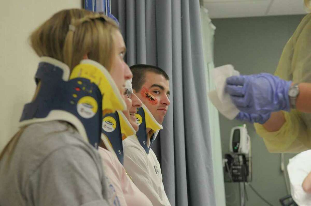 James Rizz,o a student at Glens Falls High School, playing the part of an injured patient, looks over as another student is treated during a emergency drill at Glens Falls Hospital on Tuesday morning, March 27, 2012 in Glens Falls, NY. (Paul Buckowski / Times Union)