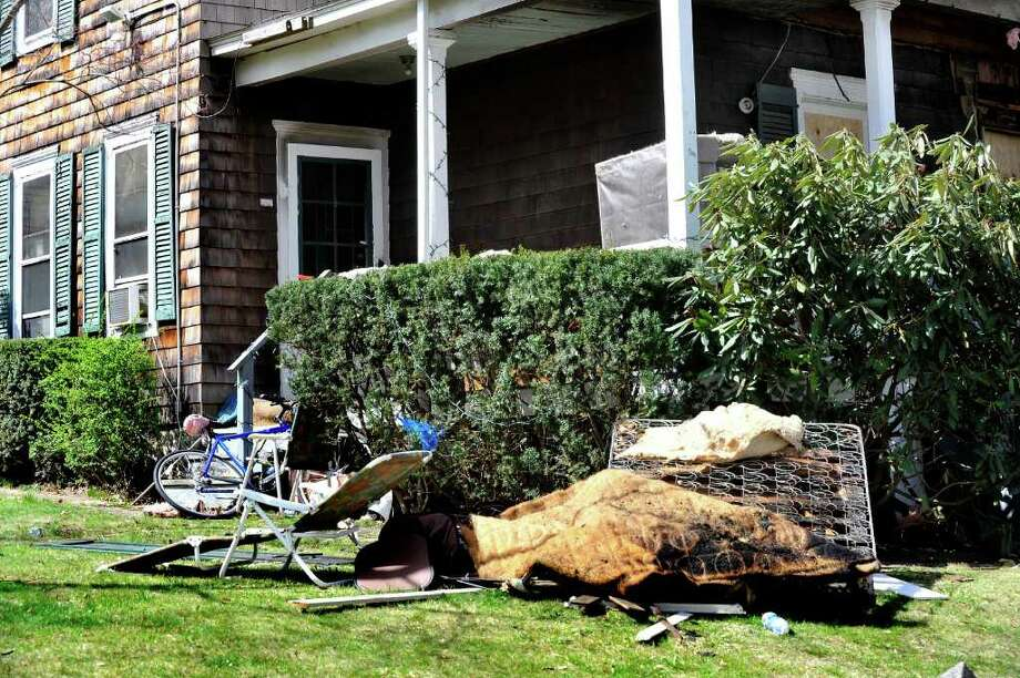 Debris lies outside the site Monday of a fatal fire at 16 Harding Place in Danbury March 26, 2012. Photo: Michael Duffy