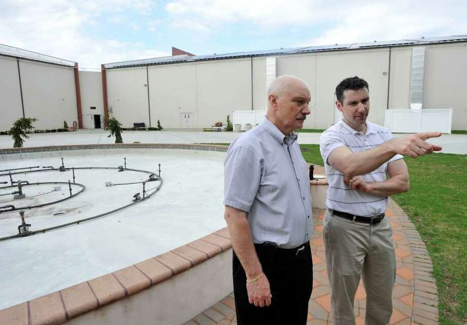 Peter D'Amico, left, listens to his son, Matt D'Amico, talk about the plans for the Veterans Honor Guard garden behind the Newtown Youth Academy on the Fairfield Hills Campus on Friday, March 23, 2012. The elder D'Amico is the director of the Newtown Youth Academy as well as president and CEO of SCB Materials International, an import-export dealer in industrial supplies. Photo: Jason Rearick / The News-Times