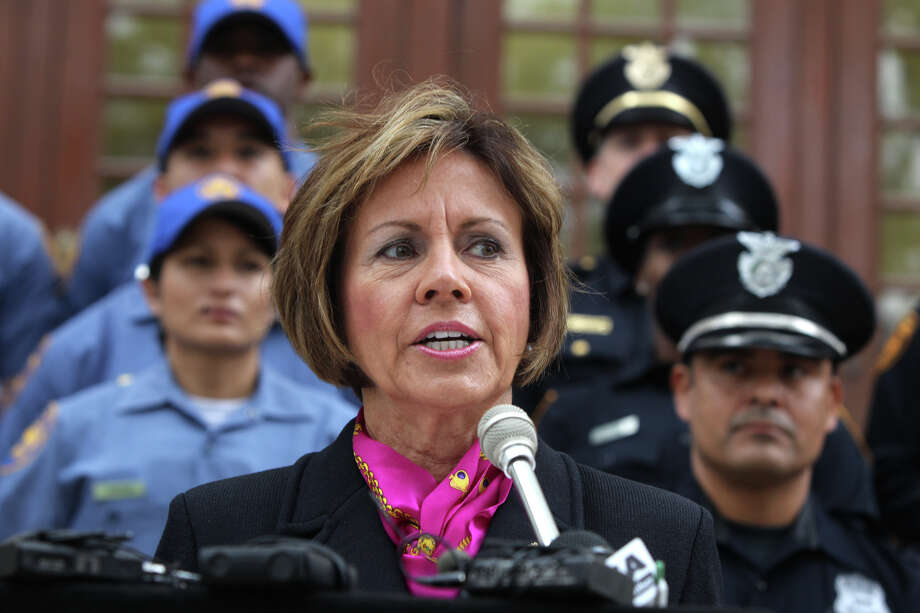 San Antonio City Manager Sheryl Sculley (front, center) speaks to the media at City Hall Tuesday March 27, 2012 about the police department's initiative to recruit new police officers in 2012. About 70 positions are available and the SAPD currently has three additional academy classes planned in 2012 (one is currently taking place). Behind Sculley are police cadets (left, light blue) and police officers (right). John Davenport/San Antonio Express-News Photo: JOHN DAVENPORT, SAN ANTONIO EXPRESS-NEWS / SAN ANTONIO EXPRESS-NEWS (Photo can be sold to the public)