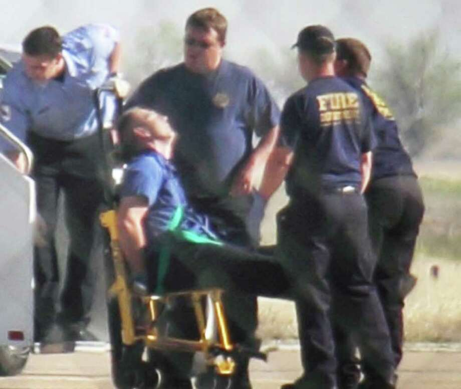 Emergency workers tend to a JetBlue captain who had to be removed in Amarillo from a Las Vegas-bound flight from New York's JFK airport. Passengers said the pilot screamed that Iraq or Afghanistan had planted a bomb on the flight. Photo: Steve Douglas, Associated Press