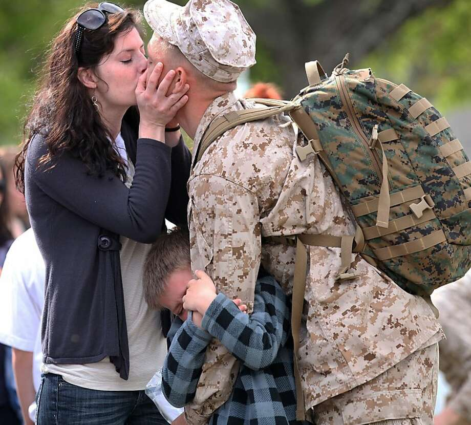 Daddy, don't go:Capt. Robert Shuford kisses his wife, Heather, goodbye as their 6-year-old son, Aden, tries hard to keep Dad from deploying with the 24th Marine Expeditionary Unit at Camp Lejeune, Jacksonville, N.C. The unit is bound for the Mediterranean and Middle East. Photo: John Althouse, Associated Press