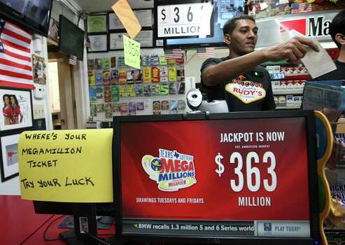 "Samir Prasla, owner/manager of Rudy's Stop & Shop, hands a customer their lottery ticket, Tuesday, March 27, 2012, in Rosenberg, where people flock to this store known as the ""biggest lottery seller in Texas"" as Mega Millions is up to $363. Photo: Karen Warren, Houston Chronicle / © 2012  Houston Chronicle"