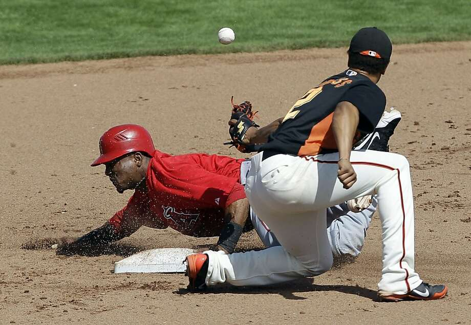 Los Angeles Angels' Erick Aybar, left, steals second base as San Francisco Giants second baseman Emmanuel Burriss misses the throw from the plate during the fifth inning of a spring training baseball game Tuesday, March 27, 2012 in Scottsdale, Ariz. Photo: Marcio Jose Sanchez, Associated Press