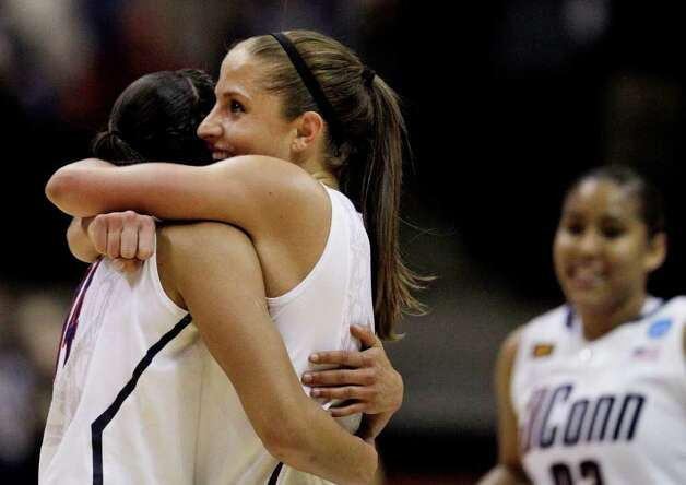 Connecticut guard Caroline Doty, center, hugs guard Bria Hartley as forward Kaleena Mosqueda-Lewis runs to them at the conclusion of an NCAA college basketball tournament regional final against Kentucky in Kingston, R.I., Tuesday, March 27, 2012. Connecticut won 80-65. (AP Photo/Stephan Savoia) Photo: Stephan Savoia, Associated Press / AP