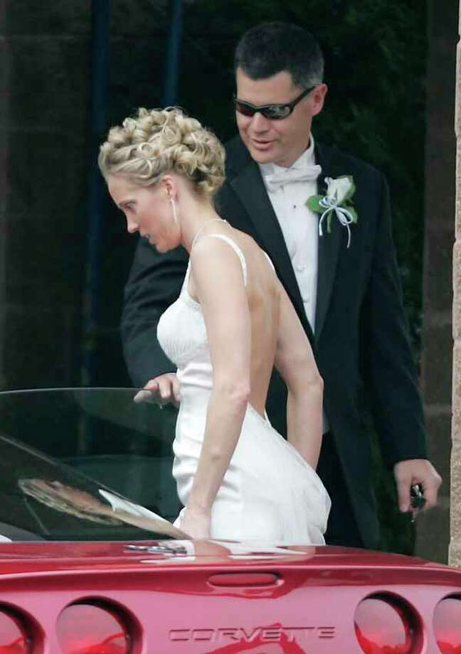 Rusty Yates opens the car door for his new bride Laura Arnold as they leave the Clear Lake Church of Christ after being married Saturday, March 18, 2006 in Clear Lake, Texas. Yates former wife, Andrea Yates, drowned their five children in a bathtub in 2001.  Her retrial on murder charges opens Monday. (AP Photo/David J. Phillip) Photo: DAVID J. PHILLIP, Houston Chronicle / AP