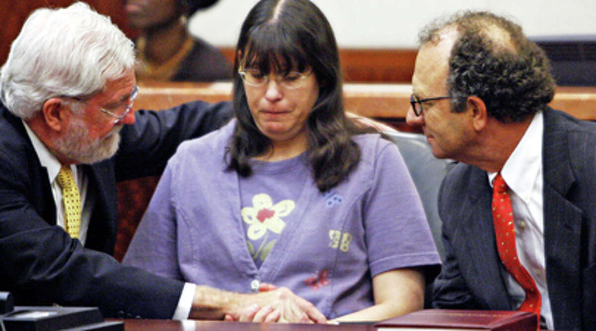 Andrea Yates, flanked by her lawyers George Parnham, left, and Wendell Odom, looks on after she was found not guilty by reason of insanity in her second murder trial for the 2001 bathtub drownings of her young children, Wednesday, July 26, 2006, in Houston.