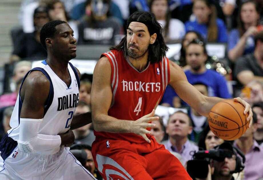 Dallas Mavericks' Ian Mahinmi, left, defends Houston Rockets' Luis Scola (4) during the first half of an NBA basketball game Tuesday, March 27, 2012, in Dallas. (AP Photo/Tony Gutierrez) Photo: Tony Gutierrez, Associated Press / AP