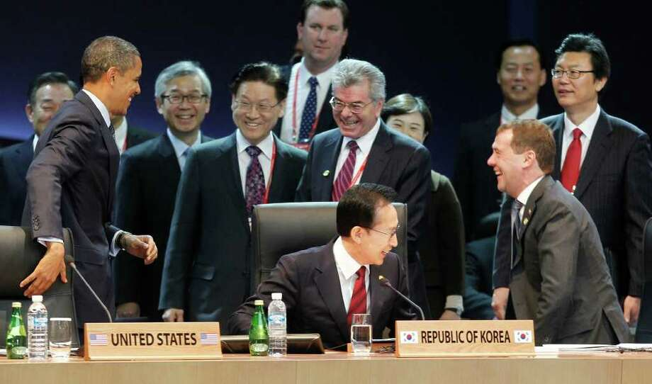 U.S. President Barack Obama, left, gets a reaction from Russian President Dmitry Medvedev, right, after jokingly covering up his microphone as they attend the opening plenary session at the Nuclear Security Summit at the Coex Center, in Seoul, South Korea, Tuesday, March 27, 2012. Sitting in the center is South Korean President Lee Myung-bak. (AP Photo/Pablo Martinez Monsivais) Photo: Pablo Martinez Monsivais