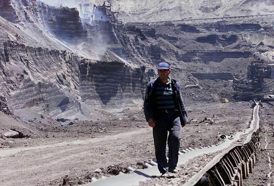 An Ethnic Albanian miner walks on top of a conveyor belt while behind him blue smoke rises from smouldering coal, at an open cast mine in Obilic, a village 10 kms (6 miles) north west of Kosovo's capital Pristina, Monday July 10, 2000. KFOR and local fire fighters are trying to extinguish the fire some 200 meters long and 30 meters high, set alight by the record temperatures in the Balkans. (AP PHOTO/Visar Kryeziu). Photo: Visar Kryeziu, ASSOCIATED PRESS