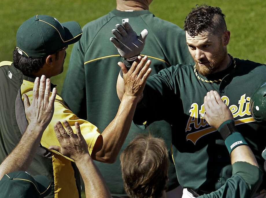 Oakland Athletics' Jonny Gomes, right, celebrates with teammates after hitting a two-run home run during the third inning of a spring training baseball game against the Seattle Mariners, Saturday, March 3, 2012, in Peoria, Ariz. (AP Photo/Charlie Riedel) Photo: Charlie Riedel, Associated Press