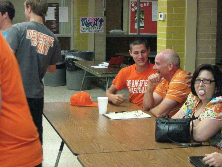 Orangefield head football coach/athletic director Brian Huckabay talks with community members and athletes at Tuesday night's board meeting.