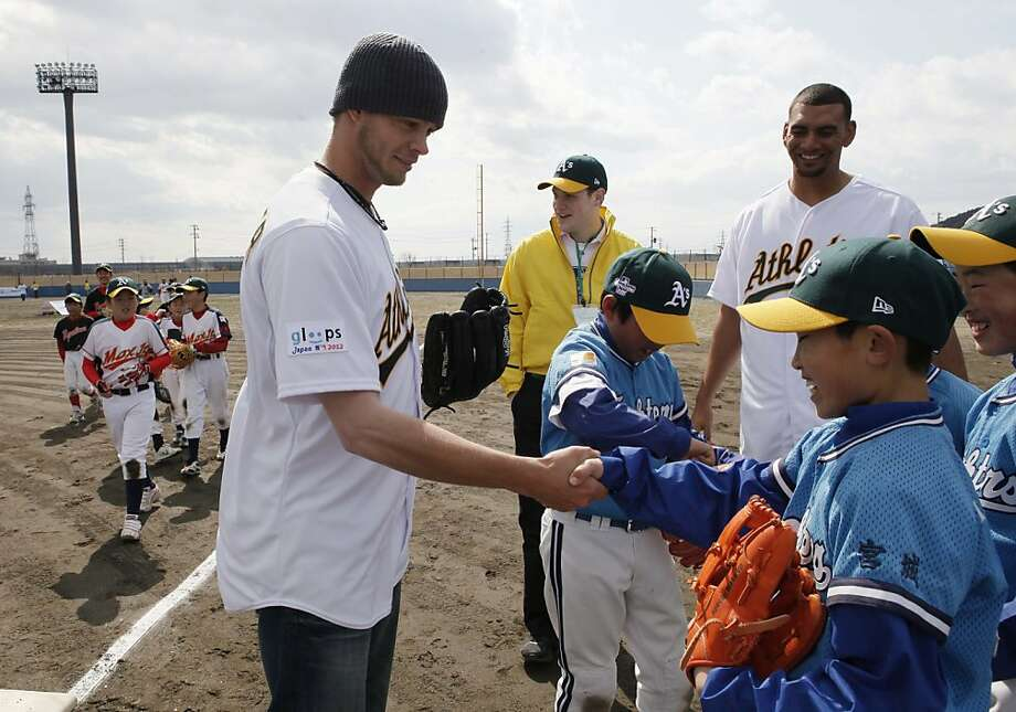Oakland Athletics pitcher Evan Scribner, left, shakes hands with a youth player during a baseball clinic by major leaguers at Ishinomaki Municipal Baseball Stadium in tsunami-hit Ishinomaki, northeastern Japan, Tuesday, March 27, 2012. The Athletics players, currently in Japan to open the MLB's 2012 season against the Seattle Mariners in Japan on Wednesday and Thursday, made a friendly visit. (AP Photo/Koji Sasahara) Photo: Koji Sasahara, Associated Press