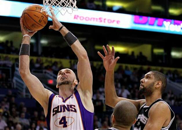 Phoenix Suns' Marcin Gortat (4), of Poland, gets past San Antonio Spurs' Tim Duncan for a score during the first quarter of an NBA basketball game Tuesday, March 27, 2012, in Phoenix. (AP Photo/Ross D. Franklin) (AP)