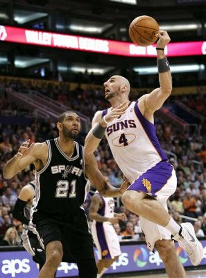 Phoenix Suns' Marcin Gortat (4), of Poland, loses control of the ball as he goes up for a shot against San Antonio Spurs' Tim Duncan (21) during the first quarter of an NBA basketball game Tuesday, March 27, 2012, in Phoenix.(AP Photo/Ross D. Franklin) (AP)