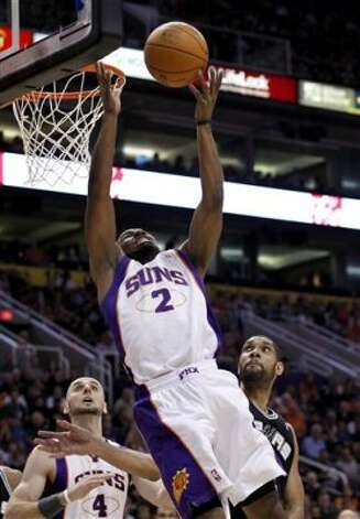 Phoenix Suns' Ronnie Price (2) gets off a shot over San Antonio Spurs' Tim Duncan, right, as Suns' Marcin Gortat (4), of Poland, watches during the second quarter of an NBA basketball game Tuesday, March 27, 2012, in Phoenix. (AP Photo/Ross D. Franklin) (AP)