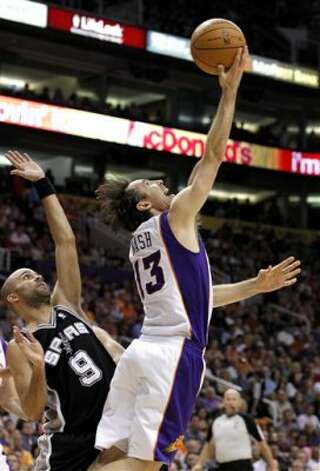Phoenix Suns' Steve Nash (13) shoots a reverse layup, and misses, in front of San Antonio Spurs' Tony Parker (9), of France, during the second quarter of an NBA basketball game Tuesday, March 27, 2012, in Phoenix. (AP Photo/Ross D. Franklin) (AP)