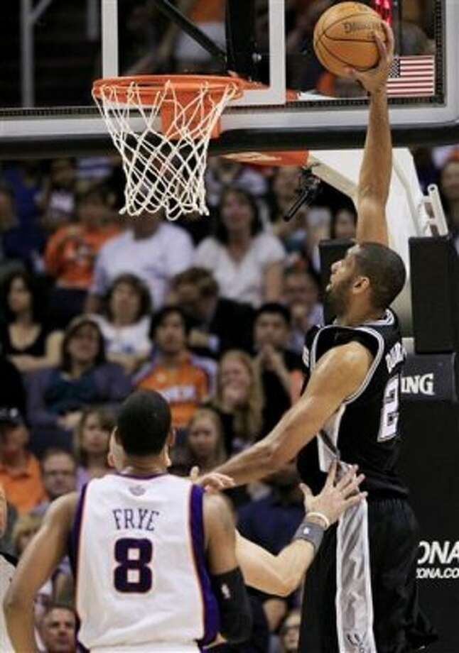 San Antonio Spurs' Tim Duncan, right, gets ready to dunk as he gets past Phoenix Suns' Channing Frye (8) and Marcin Gortat, behind Frye, during the second quarter of an NBA basketball game Tuesday, March 27, 2012, in Phoenix. (AP Photo/Ross D. Franklin) (AP)