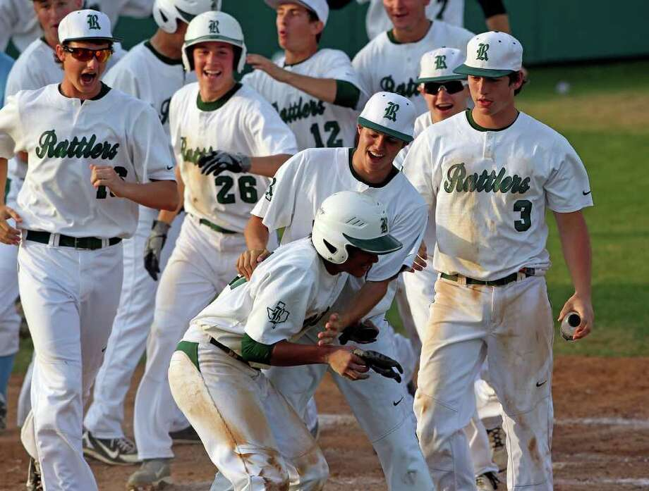 Rattler teammates congratulate Jason Sandoval on the game ending run as Reagan beats Johnson 14-4 at Blossom baseball stadium on March 27, 2012.  Tom Reel/ San Antonio Express-News Photo: TOM REEL, Express-News / San Antonio Express-News