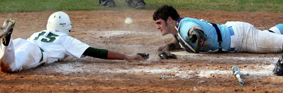 The ball gets away from Johnson catcher Connor Roy as Reagan's Drew Brooks slides over home plate to score the 14th run as Reagan beats Johnson 14-4 at Blossom baseball stadium on March 27, 2012. Tom Reel/ San Antonio Express-News