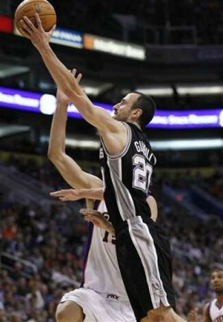 San Antonio Spurs' Manu Ginobili, front, of Argentina, beats Phoenix Suns' Robin Lopez to the basket for a score during the fourth quarter of an NBA basketball game Tuesday, March 27, 2012, in Phoenix.  The Spurs defeated the Suns 107-100.(AP Photo/Ross D. Franklin) (AP)