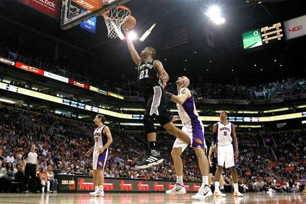 San Antonio Spurs' Tim Duncan (21) beats Phoenix Suns' Marcin Gortat, of Poland, to the basket for a score as Channing Frye (8) and Steve Nash (13) look on during the fourth quarter of an NBA basketball game Tuesday, March 27, 2012, in Phoenix.  The Spurs defeated the Suns 107-100.(AP Photo/Ross D. Franklin) (AP)