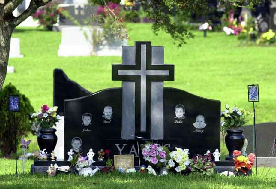 Flowers, angels and small toys sit at the base of the headstone of the five slain Yates children, Noah, John, Paul, Luke and Mary, at a Houston cemetery Tuesday, June 18, 2002, nearly one year after they were drowned by their mother, Andrea Yates.  (AP Photo/Pat Sullivan) Photo: PAT SULLIVAN, Houston Chronicle / AP