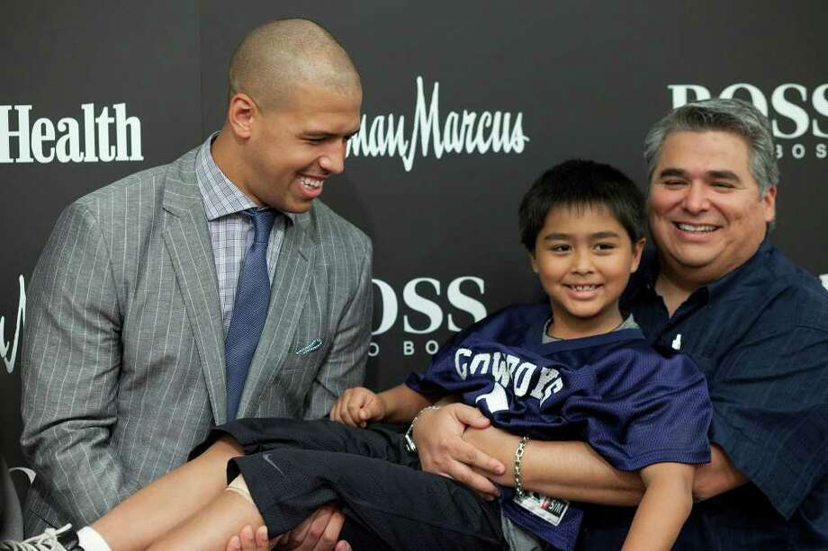 Dallas Cowboys receiver Miles Austin, from the left, gives a lift to eight-year-old Rudy Zarate, Jr., with an assist from papa Rudy Zarate at a fashion event hosted by Neiman Marcus and Hugo Boss, San Antonio, Saturday, March 24, 2012. Photo: J. Michael Short , FOR THE EXPRESS-NEWS / THE SAN ANTONIO EXPRESS-NEWS