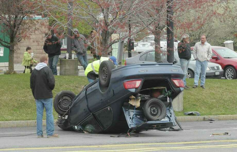 People look on as a towing company employees works at the scene of a rollover car accident at the entrance to Latham Farms on Erin Road just off Route 9 on Wednesday, March 28, 2012, in Latham, NY.  (Paul Buckowski / Times Union) Photo: Paul Buckowski