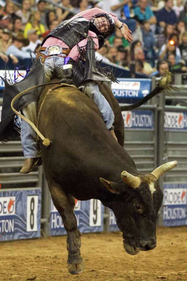 Beau Schroeder hangs on during his ride in the Super Series Championship Bull Riding at the Houston Livestock Show and Rodeo on Saturday, March 17, 2012, in Houston. Schroeder won the championship in the event. (Smiley N. Pool / Houston Chronicle ) Photo: Chronicle