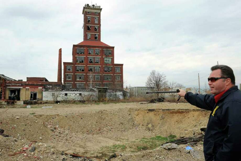 City Council member Robert Curwen points to a large crater on the Remington Arms property, in Bridgeport, Conn. March 28th, 2012. Several buildings on the site are being prepared for demolition. Photo: Ned Gerard / Connecticut Post