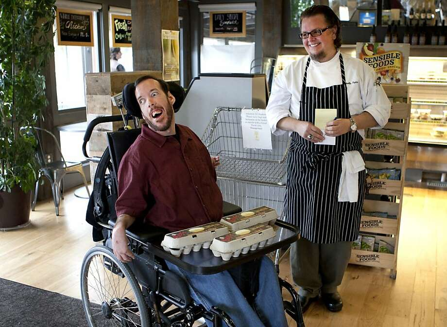 Ben Young and Charlie Ayres have a laugh inside of Calafia Cafe Town in Palo Alto on Saturday after Young delivered at crate of eggs. Ben Young, son of Neil Young, has cerebral palsy. Young  raises chickens, and sells and deliver eggs with the help of an assistant. One of Young's customers is former Google founding chef Charlie Ayers of Calafia Cafe in Palo Alto, who goes through as many as 1,500 eggs in a Sunday brunch. Photo: Kevin Johnson, The Chronicle